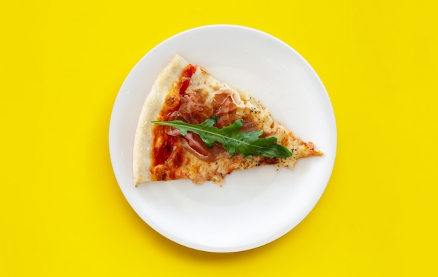 Pices of pizza on white plat on yellow background.
