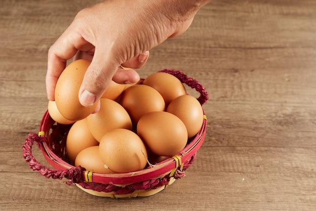테이블에 고리 버들 바구니에서 신선한 계란을 piciking