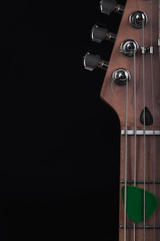 Pick on strings of electric guitar