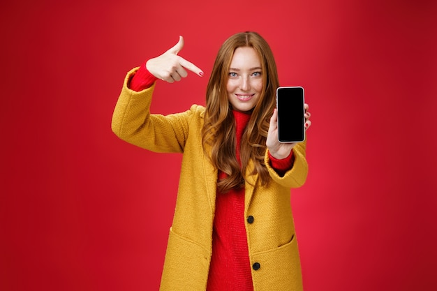Scegli questo telefono di cui non ti pentirai mai. ritratto della fidanzata glamour rossa attraente e sicura di sé dall'aspetto amichevole in cappotto giallo che mostra smartphone che punta al cellulare mentre sorride ampiamente alla telecamera.