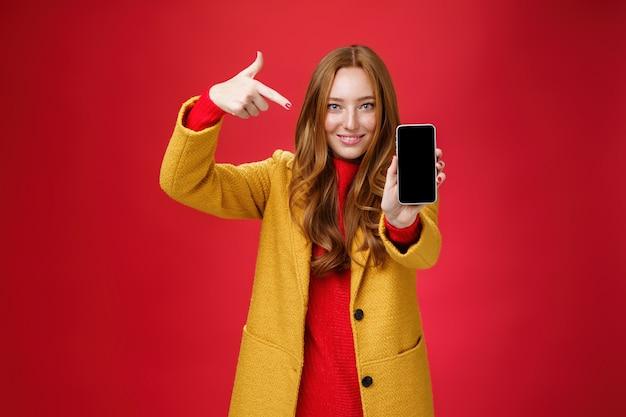 절대 후회하지 않는 휴대폰을 선택하세요. 노란색 코트를 입은 친근하고 매력적이며 자신감 넘치는 빨간 머리 매력적인 여자 친구의 초상화는 스마트폰이 카메라를 향해 활짝 웃는 것처럼 모바일을 가리키고 있습니다.