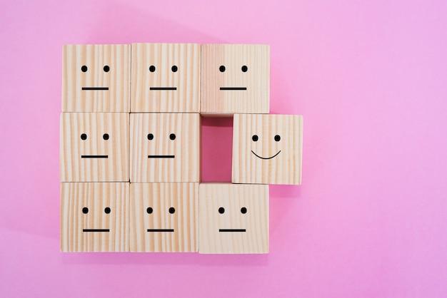 얼굴 아이콘, 고객 경험, 최고의 비즈니스 서비스 평가, 만족도 조사 개념에 미소가 있는 나무 큐브 선택