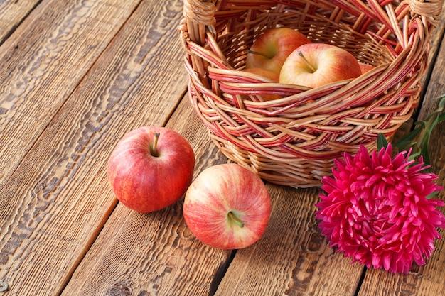 고리 버들 세공 바구니에 사과를 골랐고 오래된 나무 판자에 애스터 꽃. 방금 수확한 과일입니다. 평면도.