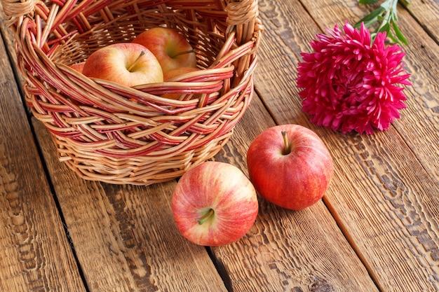 고리 버들 세공 바구니에 사과를 골랐고 오래된 나무 판자에 애스터 꽃. 방금 수확한 과일입니다.