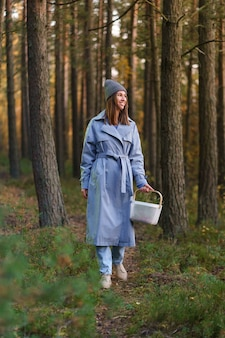 Picking season in forest young woman spend day outdoor wondering searching for mushroom and berries