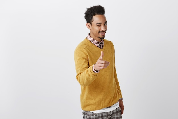 Picking you to be partner in crime. charming emotive african-american male with afro hairstyle in yellow pullover showing gun gesture, smiling broadly, greeting woman in club