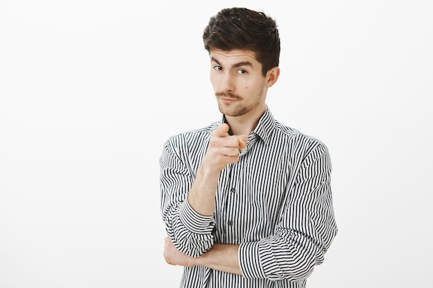 Picking you to work in my team of leaders. intrigued good-looking smart man in striped shirt, indicating with index finger, looking from under forehead with curious face, having suggestion