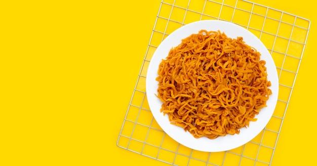 Маринованная репа в белой тарелке на желтом фоне.