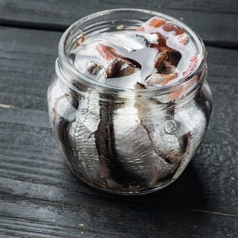 黒い木製のテーブルの上に、ガラスの瓶に入れたアンチョビのピクルス セット