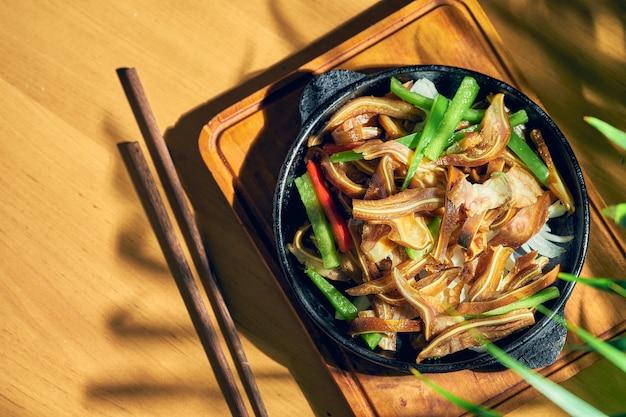 프라이팬에 절인 및 튀긴 돼지 귀. 중국 요리.