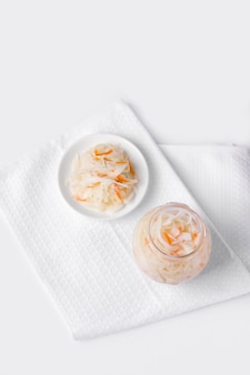 매리 네이드의 항아리 옆에 접시에 절인 양배추와 당근. 발효 식품. 흰 배경.