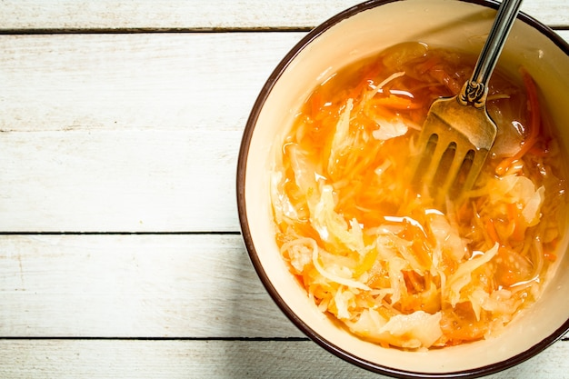 Pickled cabbage in a bowl. on a white wooden background.