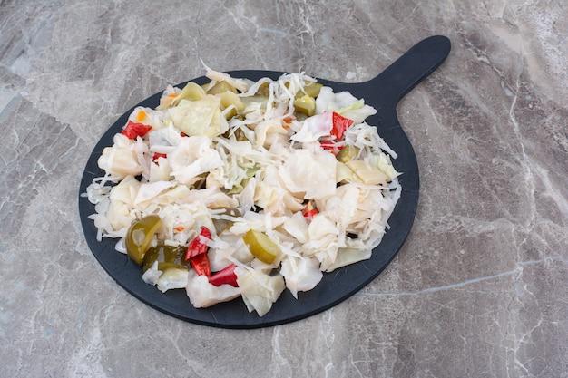Cavolo marinato con varie verdure a bordo scuro.