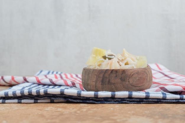 Маринованная капуста с ломтиками овощей в деревянной миске