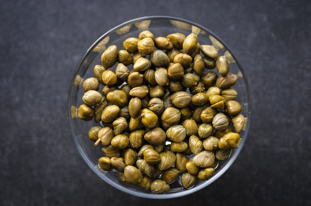 Pickled capers in a glass bowl on dark, top view close up