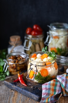 Pickled cauliflower with carrots in a glass jar on a dark wooden table.