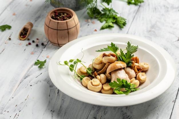 나무 배경에 후추와 파슬리를 곁들인 절인 샴피뇽 버섯, 배너, 메뉴, 텍스트를 위한 레시피 장소, 위쪽 전망,