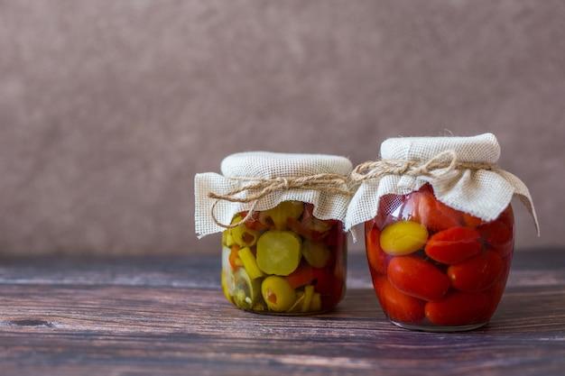 Маринованные помидоры черри и салат из консервированных огурцов в стеклянных банках на деревянном фоне