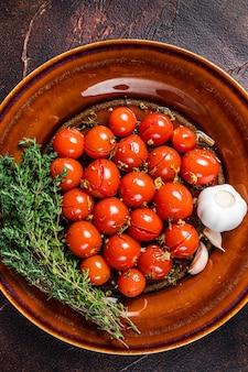 마늘과 백리향과 함께 소박한 접시에 절인된 체리 토마토. 어두운 배경입니다. 평면도. 공간을 복사합니다.