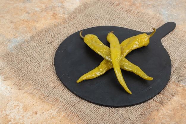Peperoncini marinati sul bordo nero con tela da imballaggio