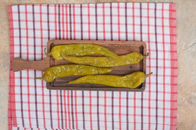 Маринованный перец чили на деревянной доске со скатертью
