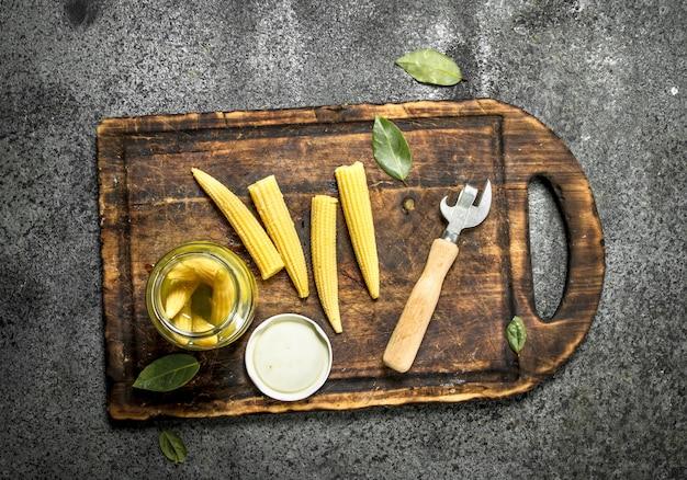 まな板の上の瓶に漬けたトウモロコシ。素朴な背景に。