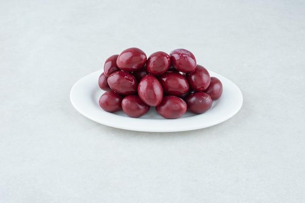 Маринованные кизиловые вишни на белой тарелке.