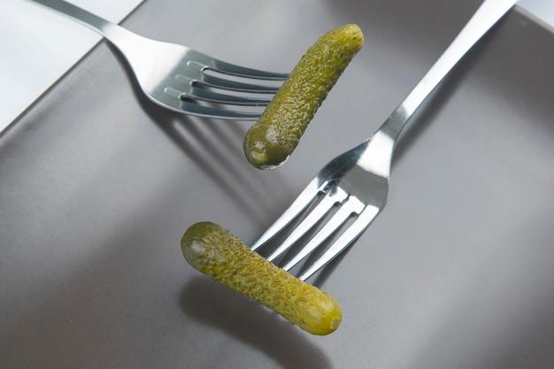 포크에 절인 오이. 음식과 야채