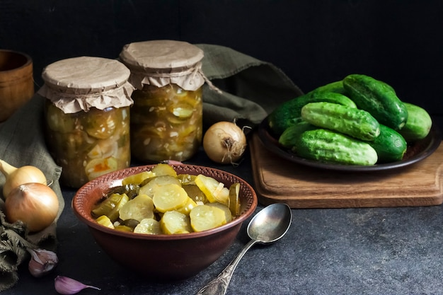 Pickled cucumber salad in a bowl and jars on black background