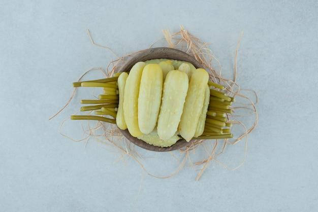 Маринованные огурцы и стручковая фасоль в деревянной миске.