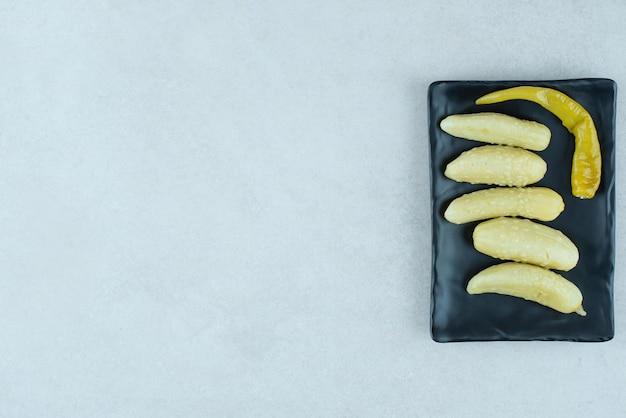 Маринованные огурцы и перец на черной тарелке.