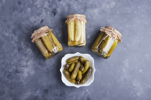 Pickled cucumbers in bowl and glass jars on blue background.