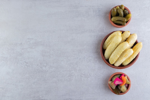 Pickled cucumbers in bowls placed on stone background.