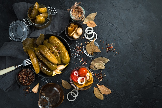 Pickled cucumbers in a ceramic round plate on a black background. top view with copy space.