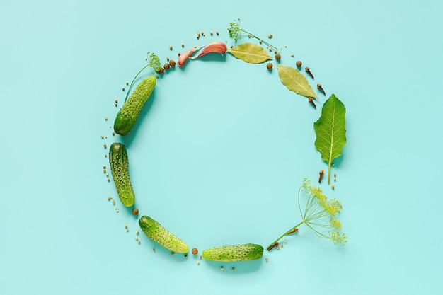 Pickled cucumbers. circle frame with copy space from ingredients for marinated gherkins on blue background.