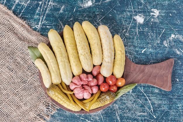 Маринованные огурцы, чеснок, перец и помидоры на деревянной тарелке.