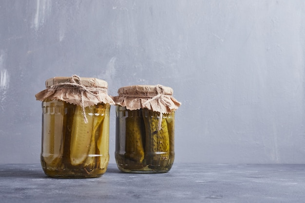 Pickled cucumbers in glass jars on blue background.