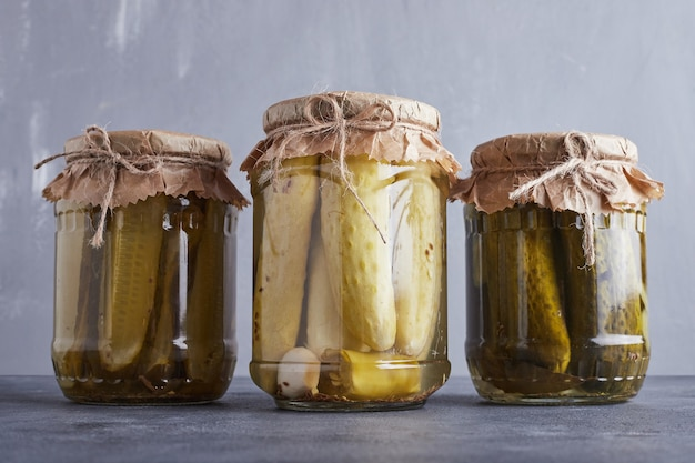 Pickled cucumbers in glass jars on blue wall.