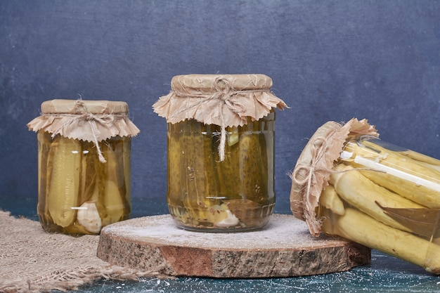 Pickled cucumbers in glass jars on blue.