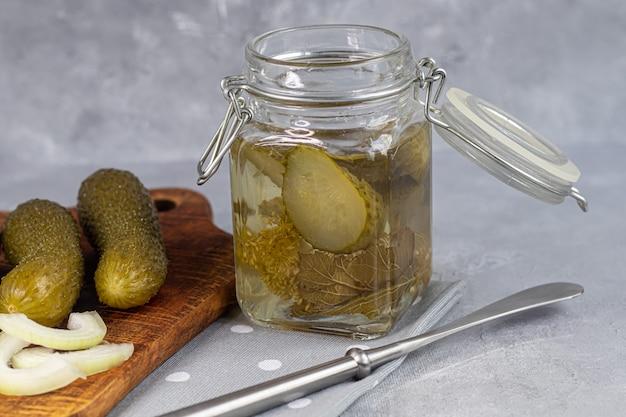 ガラスの瓶と木の板に漬けたきゅうり。灰色の背景に発酵食品。スペースをコピーします。