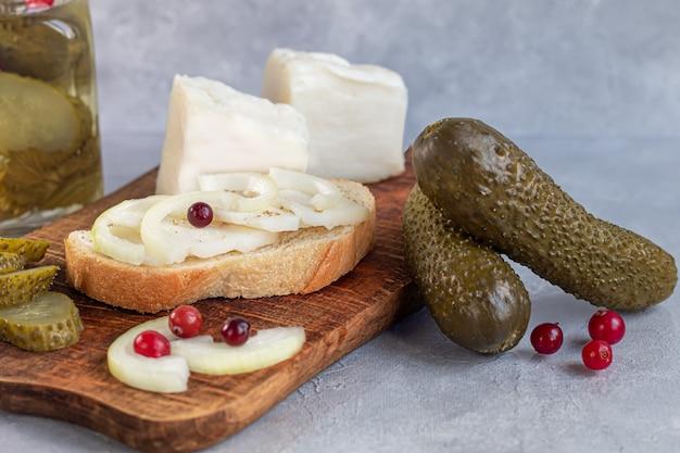 きゅうりのピクルスを木の板のガラス瓶に入れ、ベーコンのサンドイッチ。バックグラウンドでマスタード豆。発酵食品。スペースをコピーします。