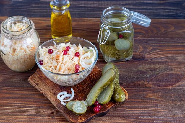 きゅうりのピクルスを木の板のガラス瓶に入れ、ザワークラウトとクランベリーを添えて。発酵食品。スペースをコピーします。