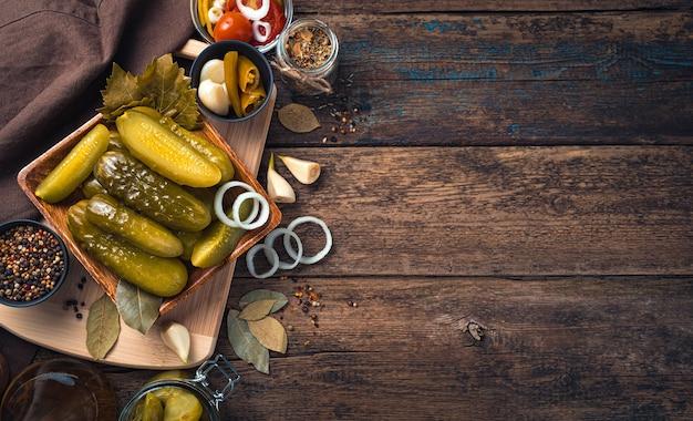 Маринованные огурцы в деревянной тарелке на разделочной доске со специями. домашние соленья.