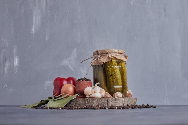 Маринованные огурцы в стеклянной банке с листом, чесноком, луком и зерновым перцем.