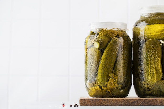 Pickled cucumbers in jars on a white background canning vegetables copy space