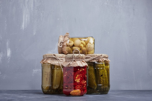 Pickled cucumbers, olives and red peppers in glass jars on blue background.