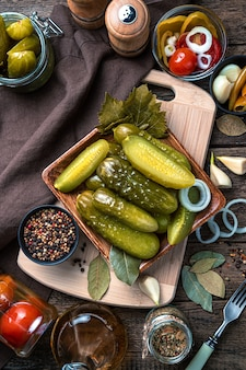 Pickled cucumbers, onions, garlic and spices on a wooden background. top view, vertical.