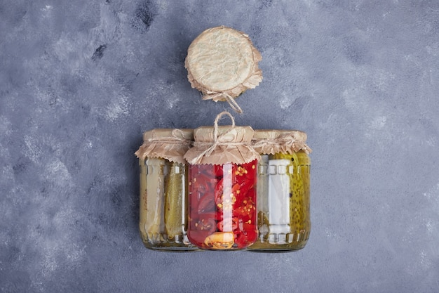 Pickled cucumbers and red peppers in glass jars on blue background.