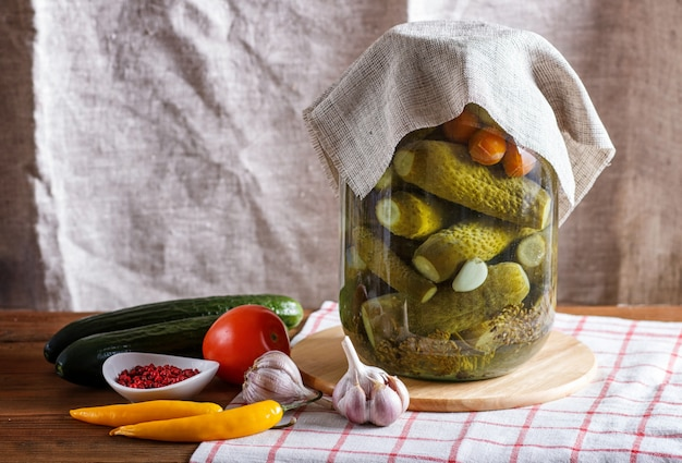 Pickled cucumbers and tomatoes in a glass jar on linen tablecloth and wooden table.