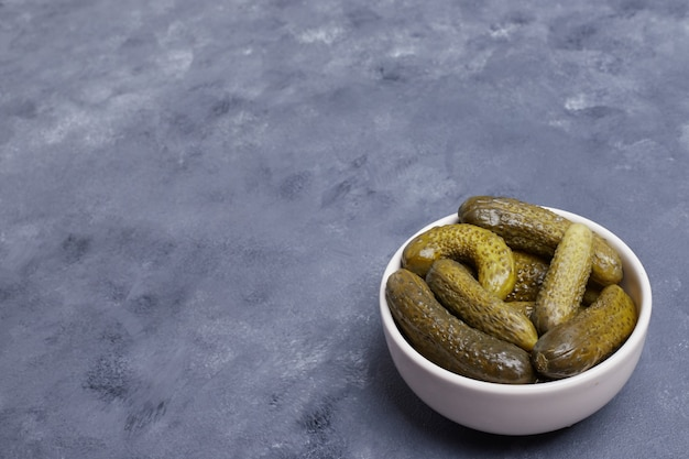 Pickled cucumbers in white bowl on blue background.